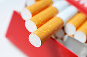 Pack of cigarettes in red box with filters in focus
