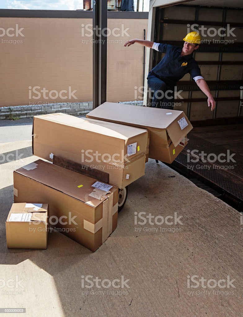 Package Delivery Dock Rude Worker Kicking Cardboard Boxes stock photo