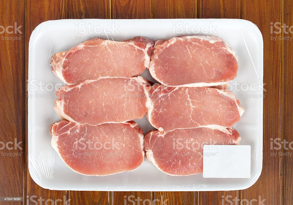 A package of fresh meat on a wooden surface stock photo