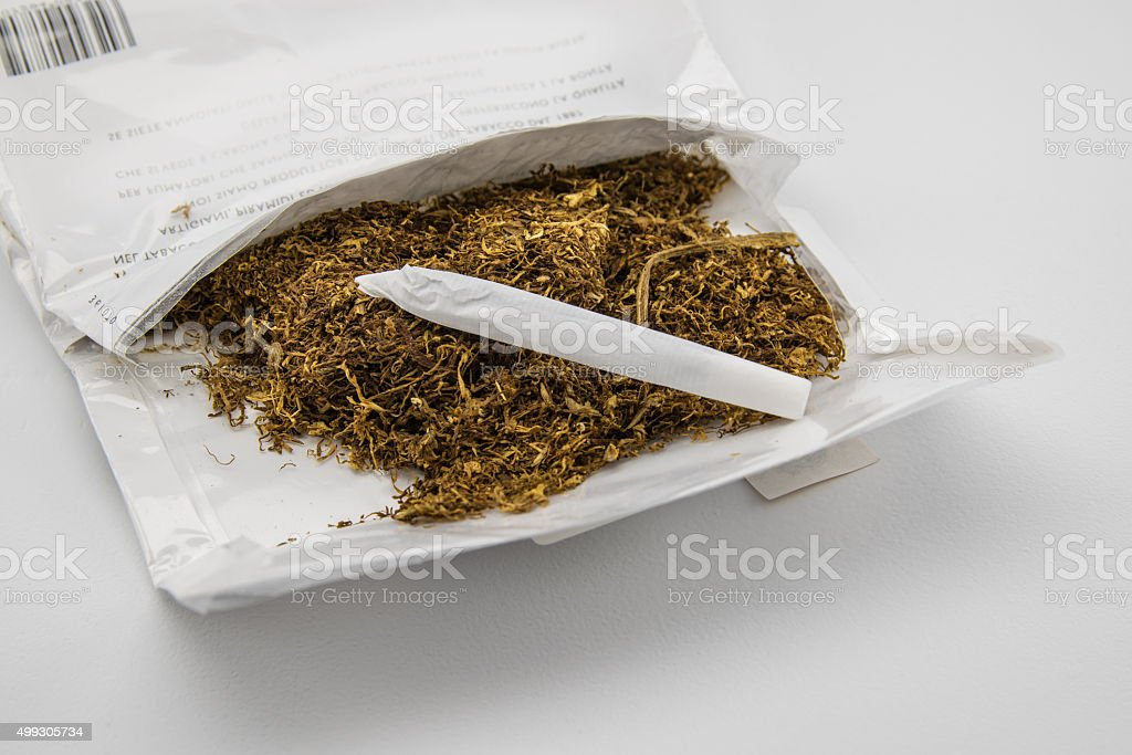 package of tobacco and hand made cigarette stock photo