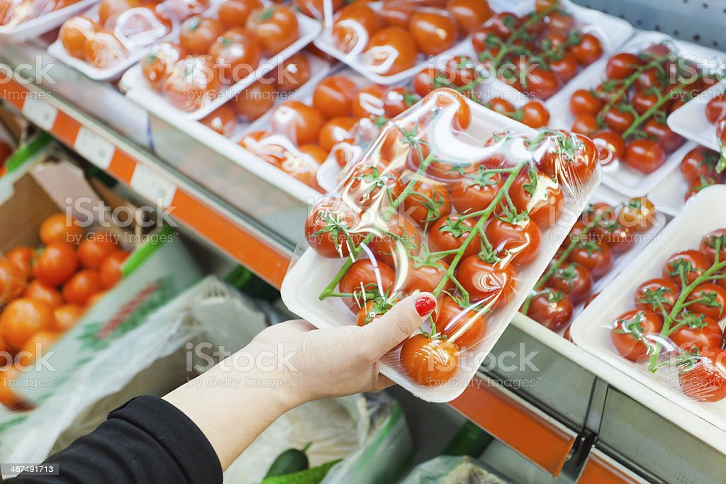 Packaged tomato with woman hand in the supermarket stock photo