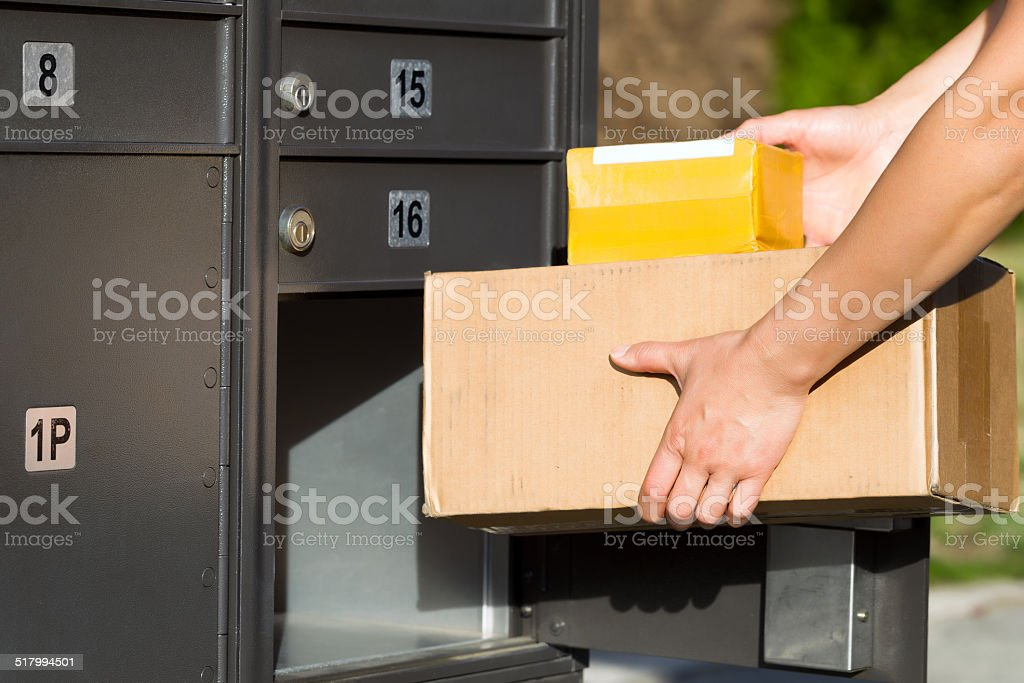 Packages being loaded into postal mailbox stock photo