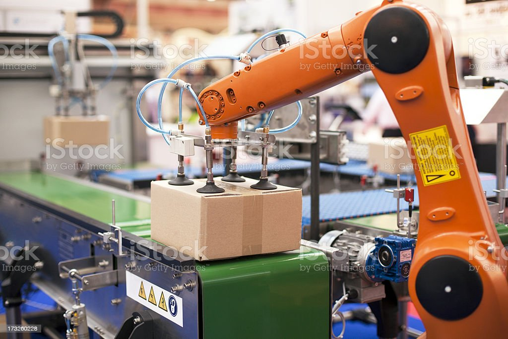 Packaging line with robotic arm at work stock photo