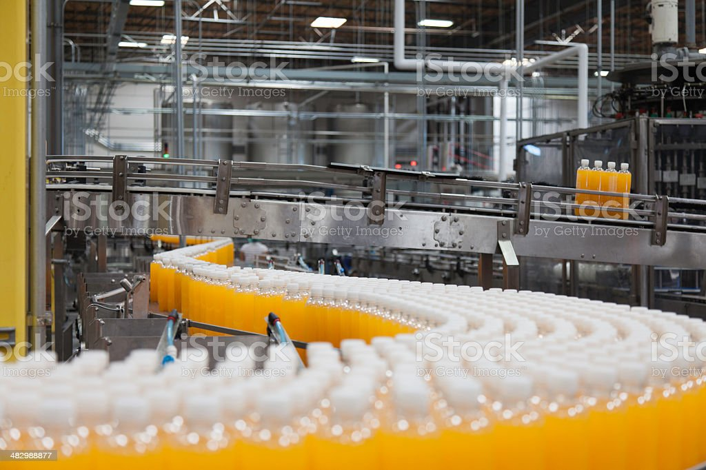 Packed bottles moving on conveyor belt stock photo
