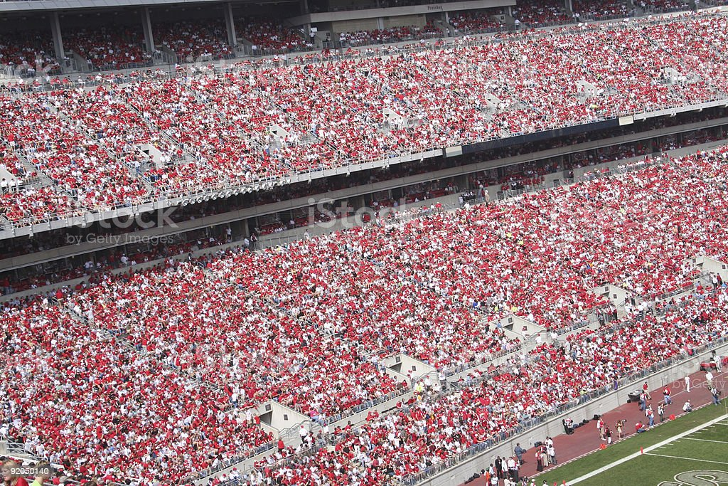 Packed football stadium focused on crowd wearing red stock photo