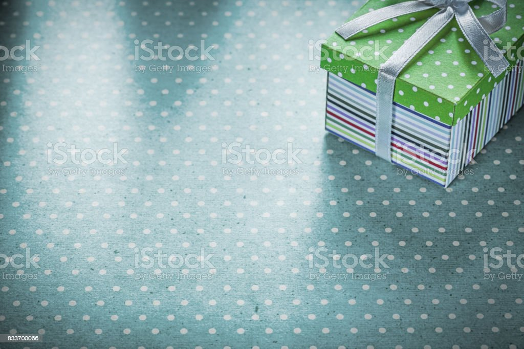 Packed gift on blue polka-dot tablecloth holidays concept.