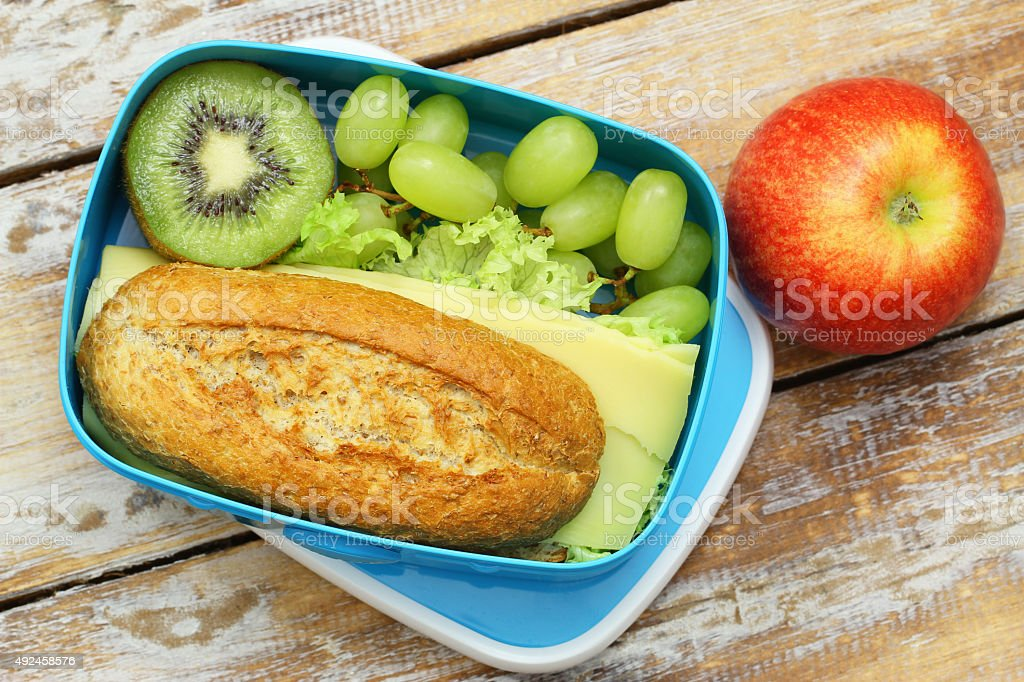 Packed lunch box containing brown cheese roll, grapes, kiwi, apple stock photo
