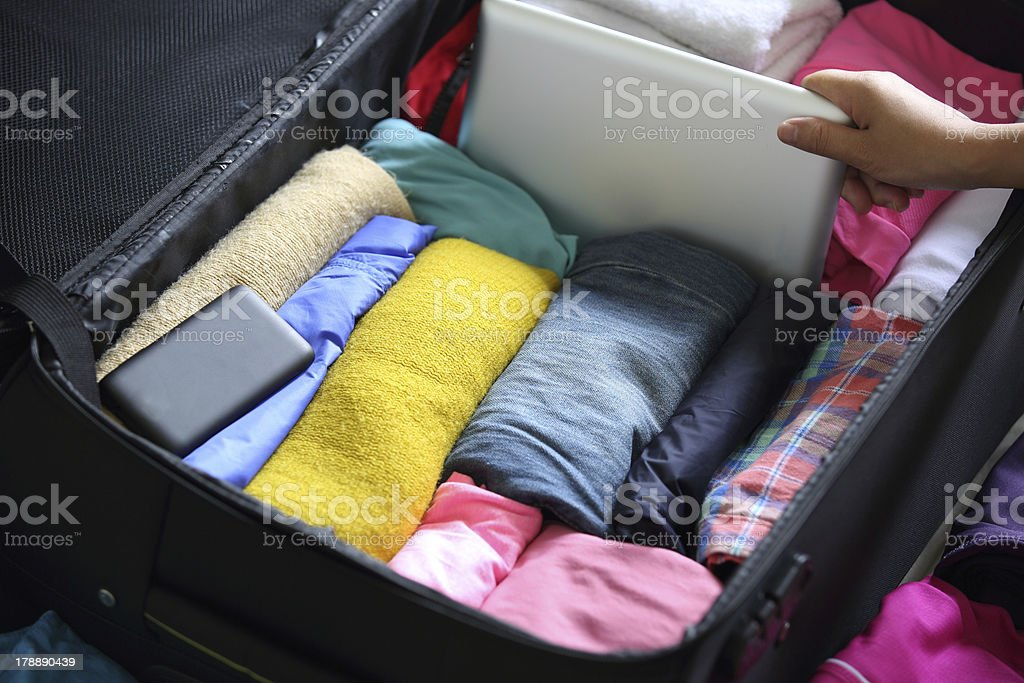 A packed suitcase with well folded clothes and electronics  stock photo