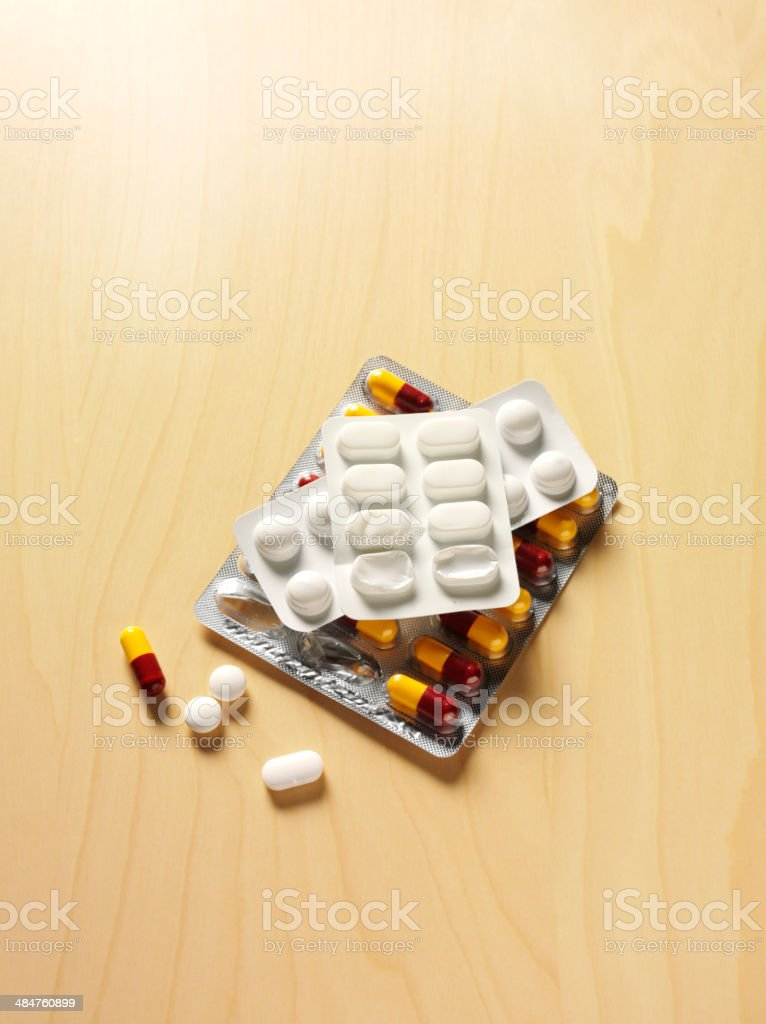 Packets of Medical Tablets on a wooden Desk stock photo