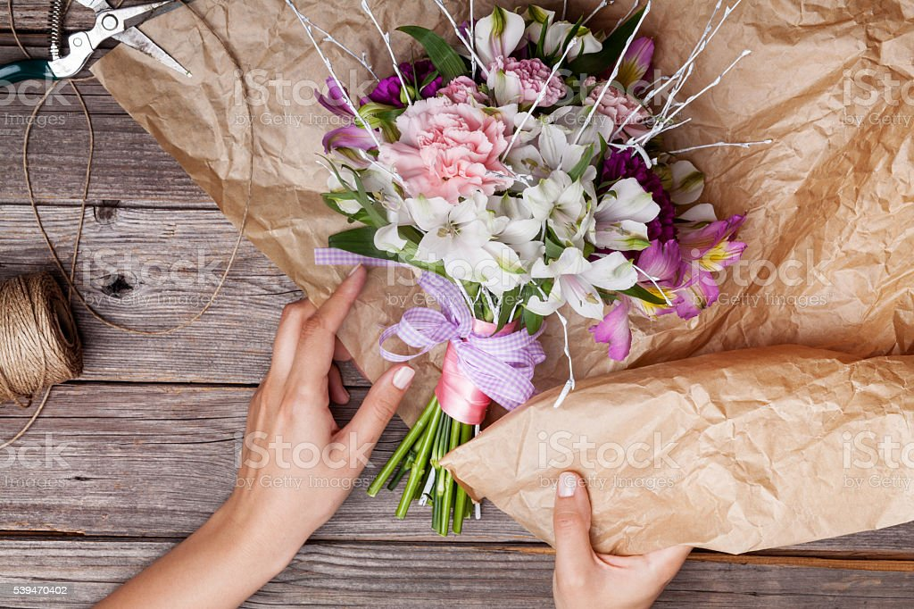 Packing a rustic bouquet from gillyflowers and alstroemeria on o stock photo