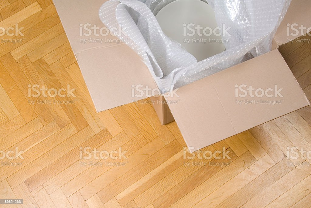 Packing plates with protective bubble wrap and cardboard box royalty-free stock photo