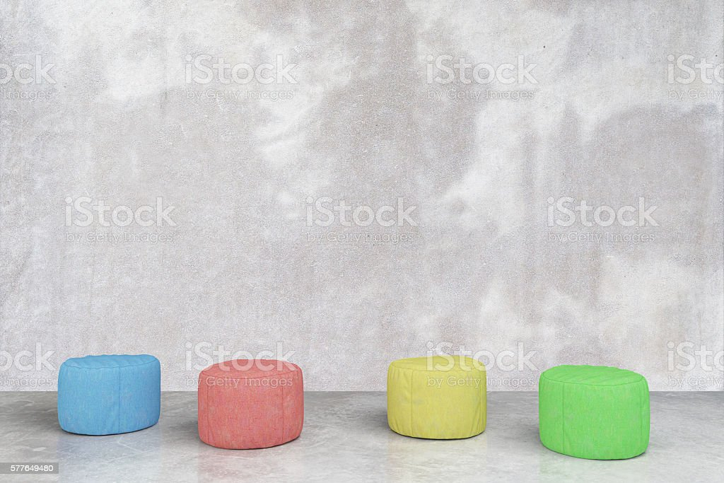 Padded stools in concrete room stock photo