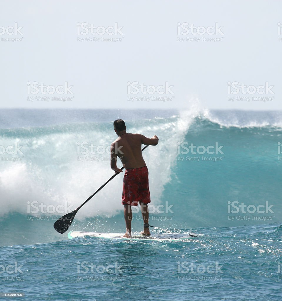 A paddle boarder about to catch a big wave royalty-free stock photo