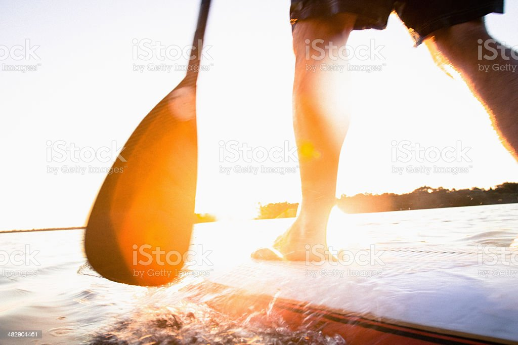 Paddle boarder in shallow water at sunset stock photo