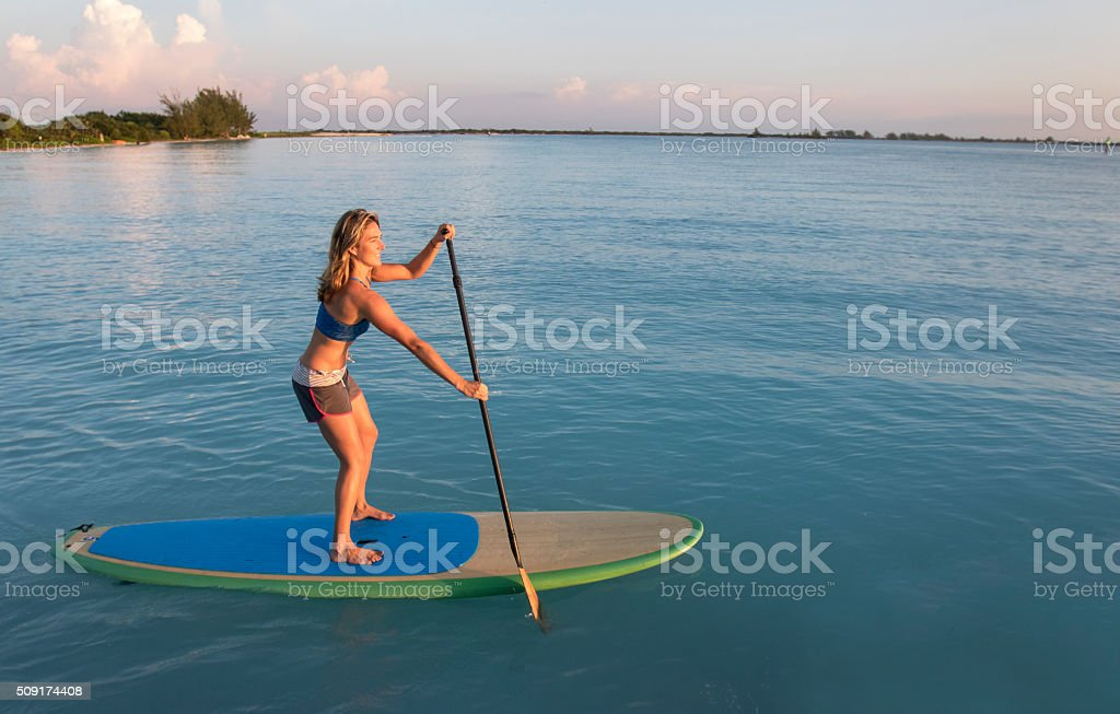 Paddle Boarding Woman on a Calm Ocean Bay stock photo