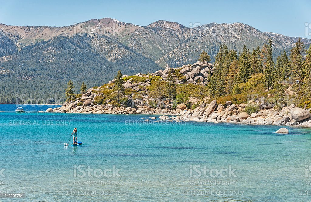 Paddle Boater towing Intertuber Lake Tahoe Sand Harbor stock photo