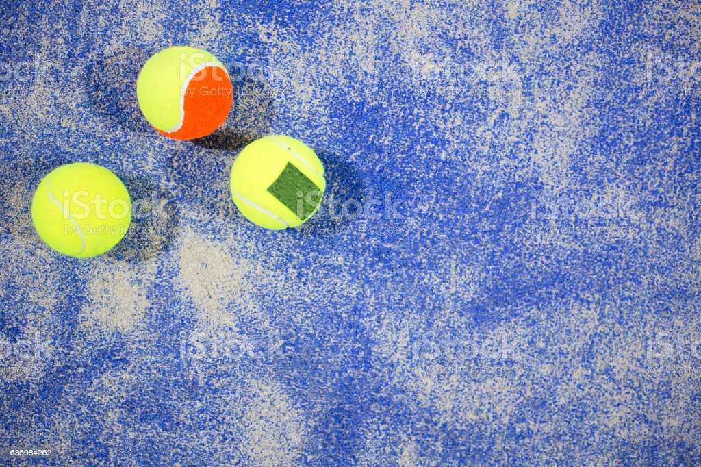 Paddle tennis balls on blue turf in court. stock photo