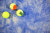 Paddle tennis balls on blue turf in court.