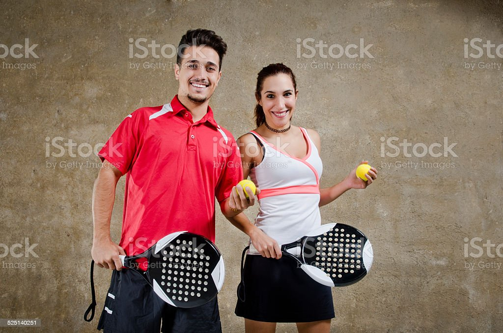 Paddle tennis couple posing in concrete court stock photo