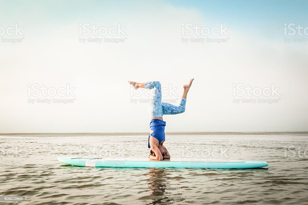 Paddleboard Headstand Bent Knees stock photo