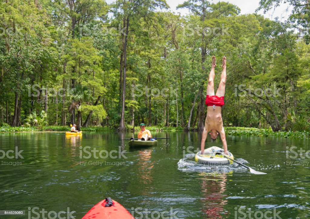 Paddleboarding and Handstand stock photo