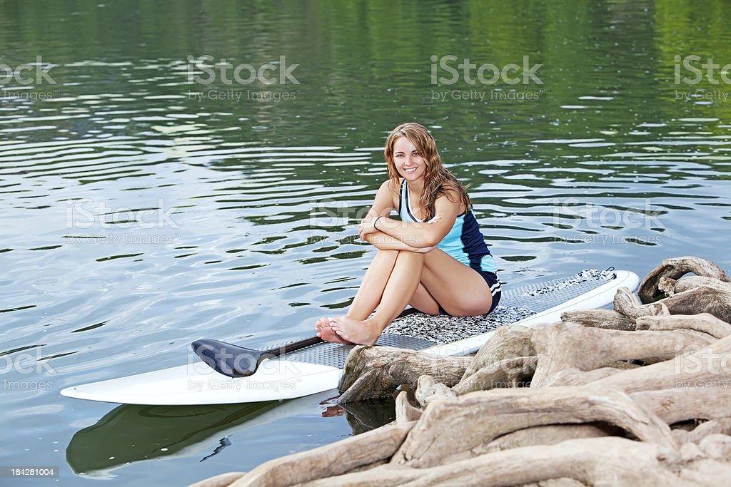 paddleboarding female sitting on a paddleboard stock photo