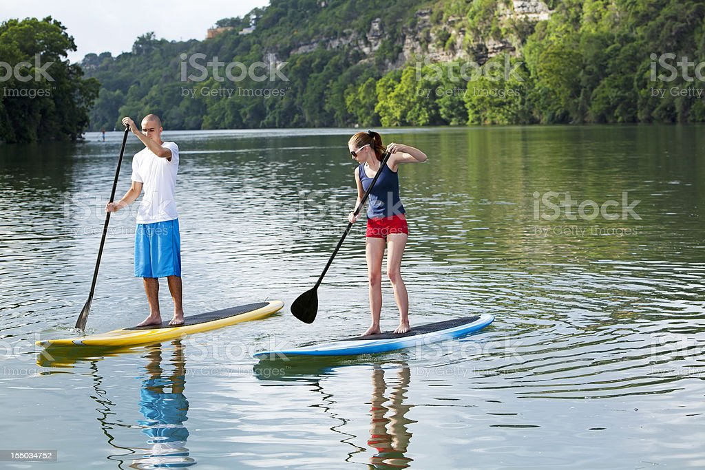 paddleboarding  male and female stand up paddling royalty-free stock photo