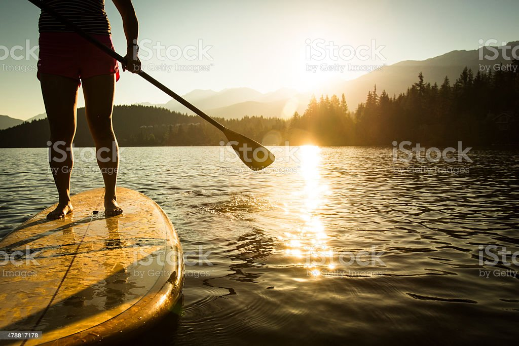 Paddleboarding on lake during sunrise or sunset. stock photo