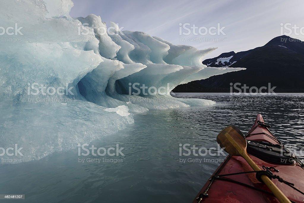 Paddler pauses to look at Melting Iceberg stock photo