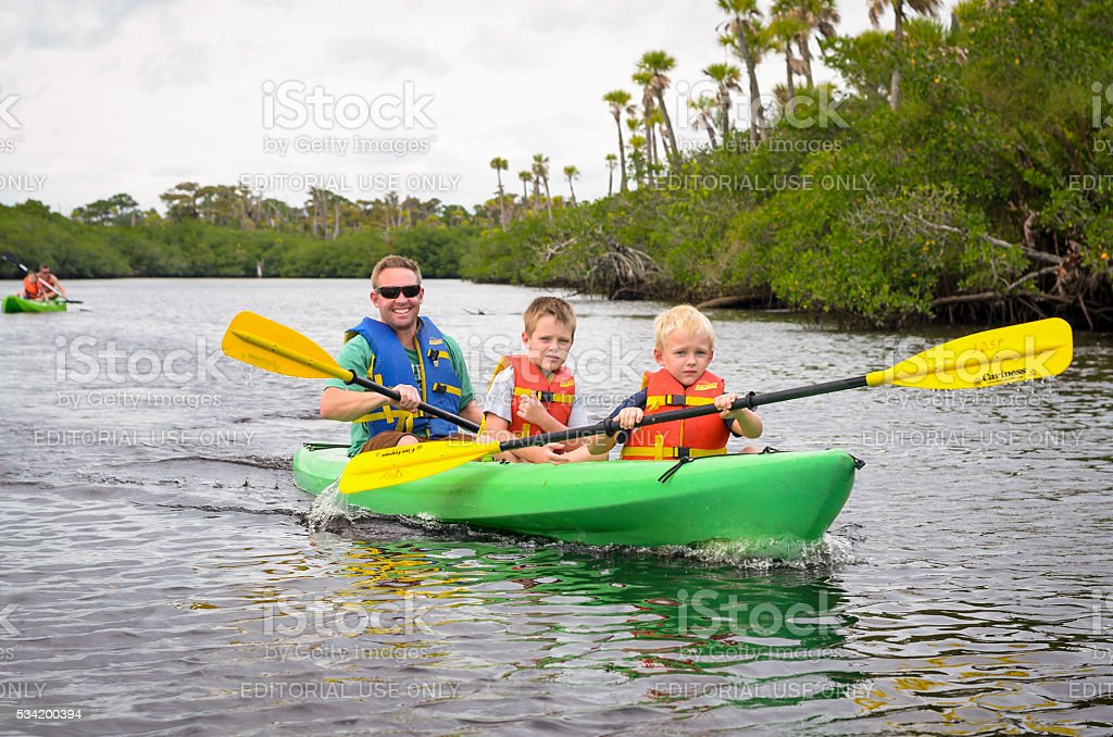 Paddling in a green canoe stock photo