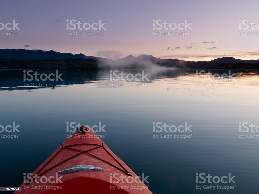 Paddling in a kayak through calm sunset waters royalty-free stock photo