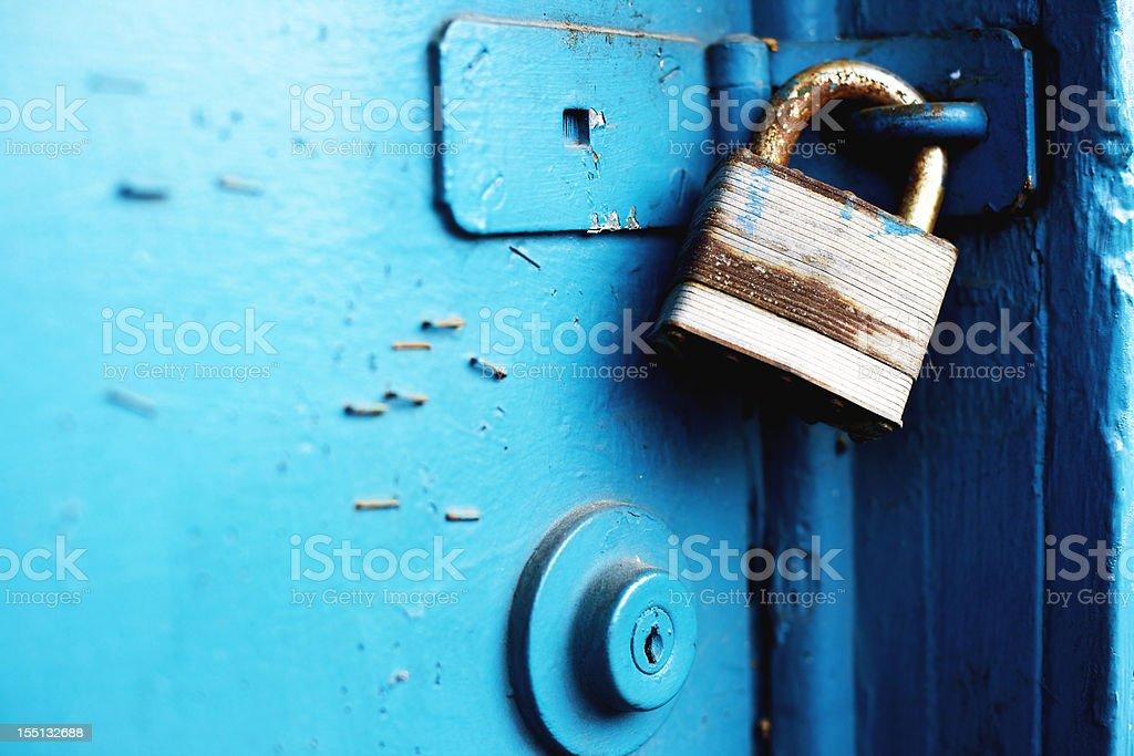 padlock and entry locks on blue door stock photo