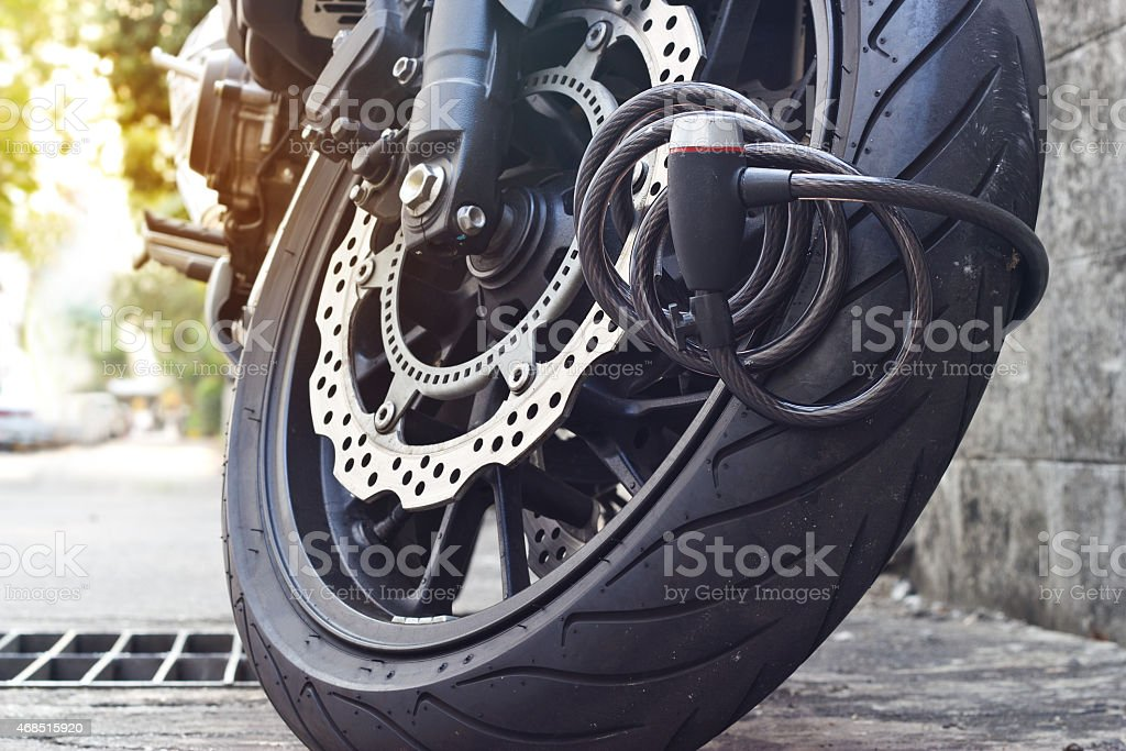padlock security lock blocking the motorcycle wheel on street stock photo