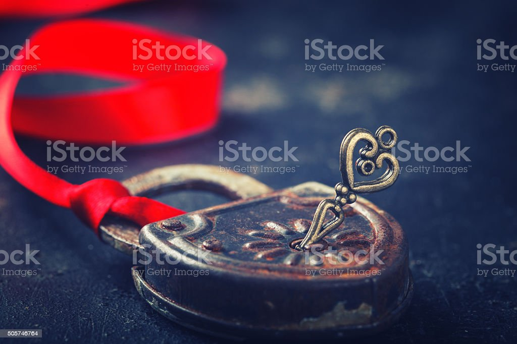 Padlock with key and a red ribbon stock photo