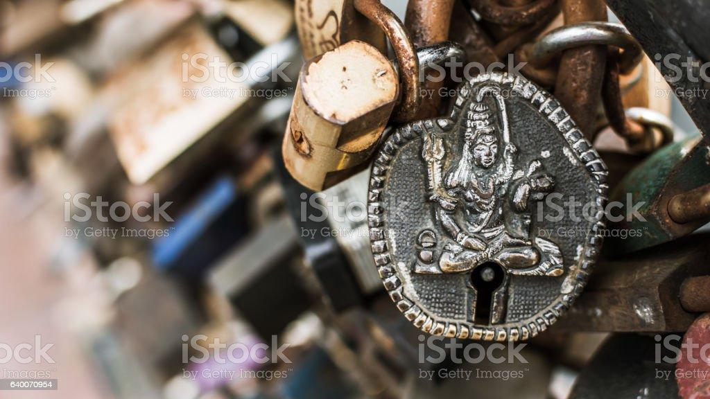 Padlock with Vishnu image among other rusty padlocks. stock photo