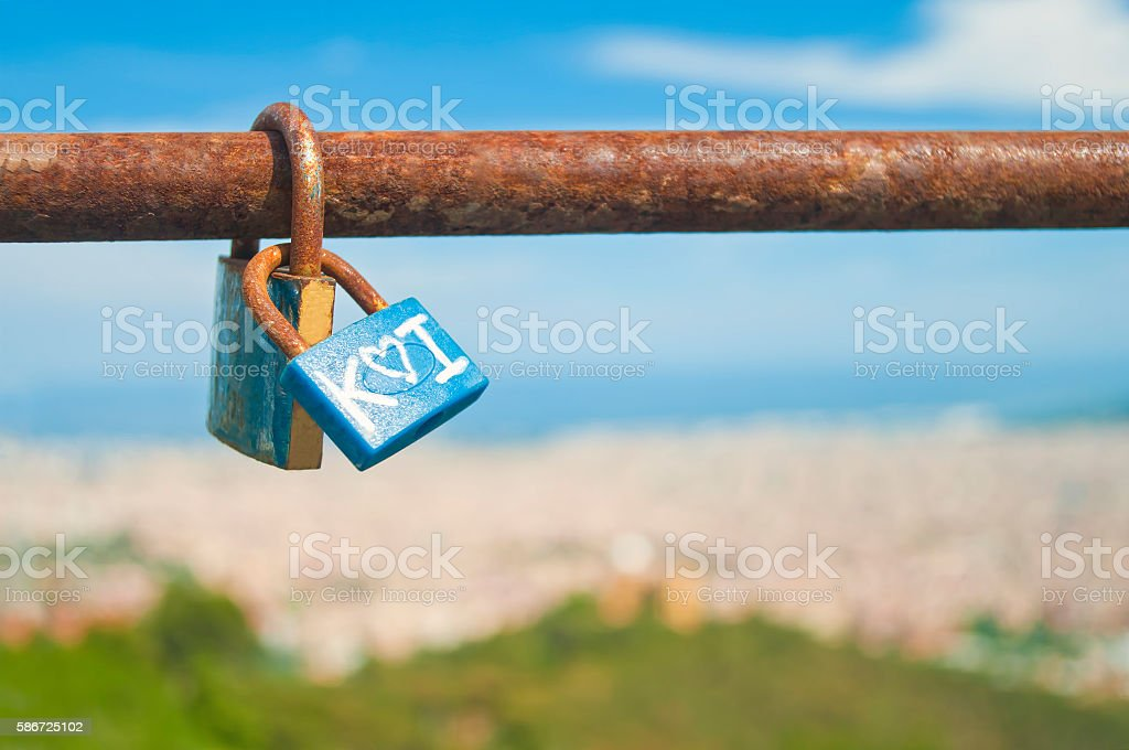 padlocks on rusty bar with cityscape at background stock photo