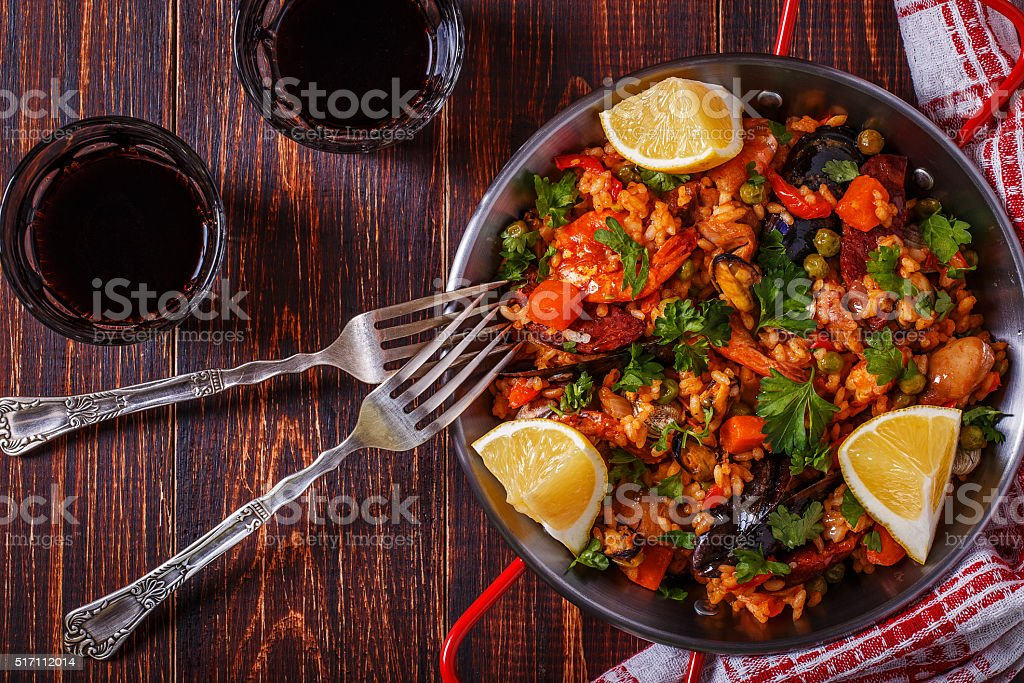 Paella with chicken, chorizo, seafood, vegetables and saffron. stock photo