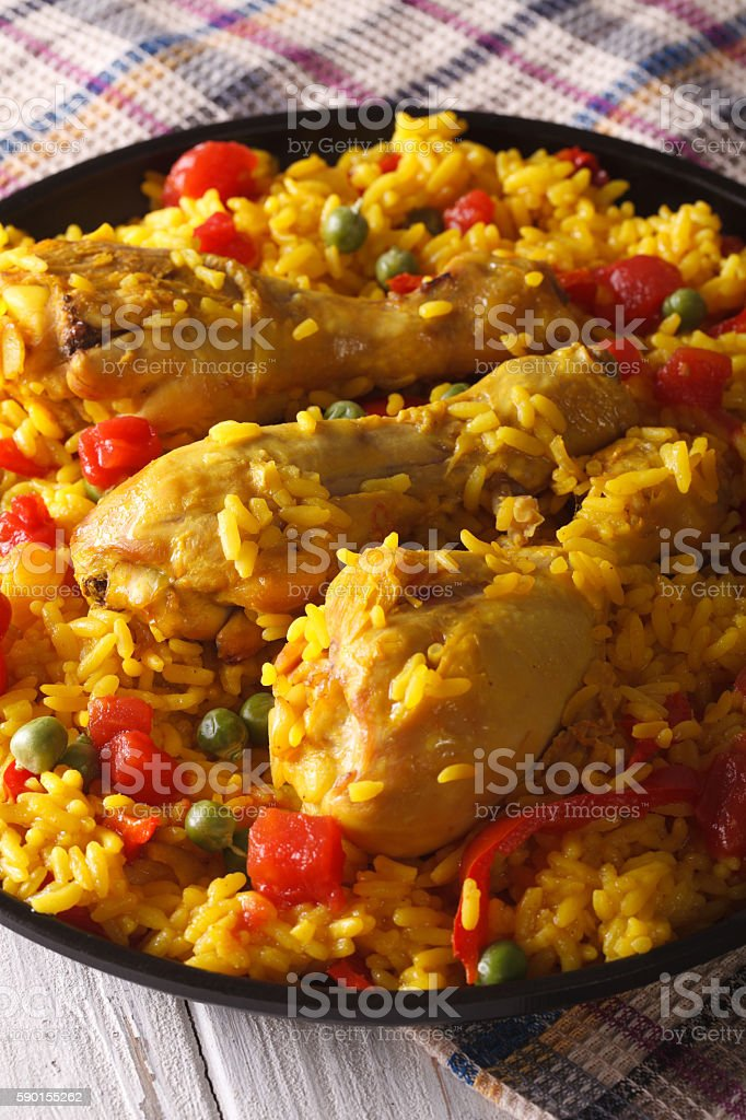Paella with chicken legs and vegetables close-up. Vertical stock photo