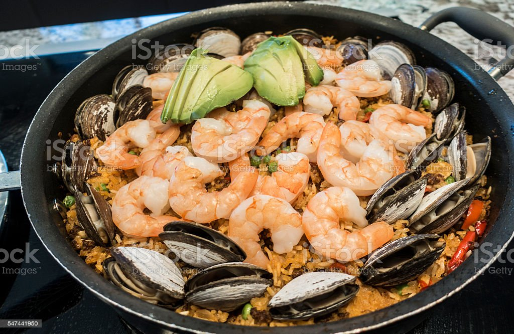 Paella With Shrimp, Clams, Avocado, Spanish Rice, Garlic, Paprika, Saffron stock photo