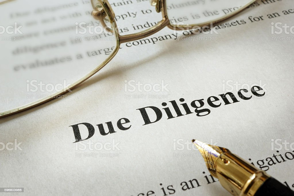 Page of paper with words Due Diligence and glasses. stock photo