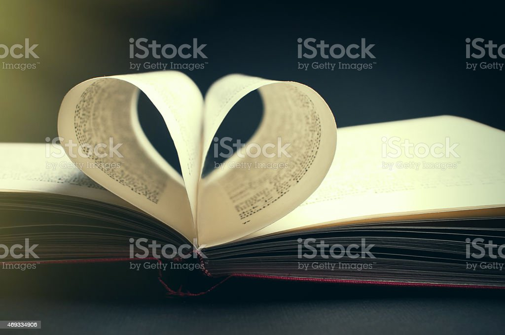 pages of a book curved into a heart shape stock photo