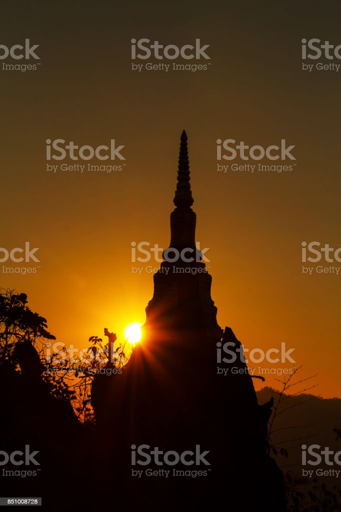 Pagoda silhouette on rock in golden sunlight shade at dawn or dusk stock photo