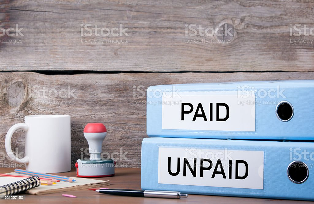 Paid and Unpaid. Two binders on desk in the office stock photo