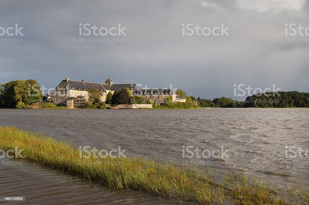 Paimpont abbey viewed from the lake with a beautiful sky stock photo
