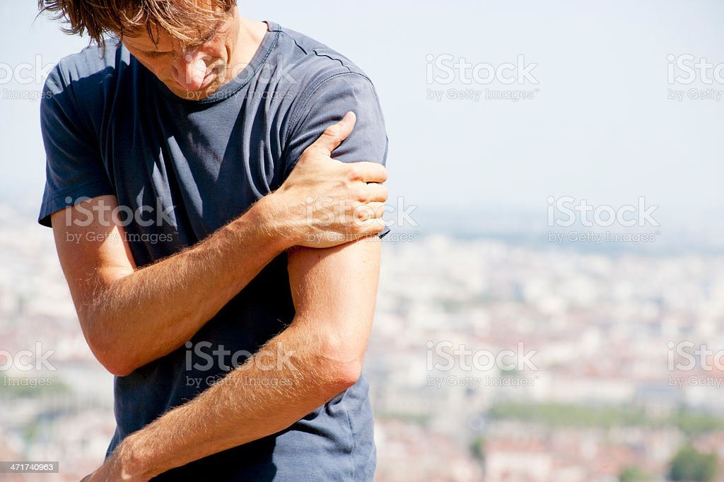 Pain in left upper arm stock photo