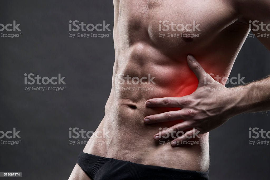 Pain in the left side. Muscular male body. stock photo