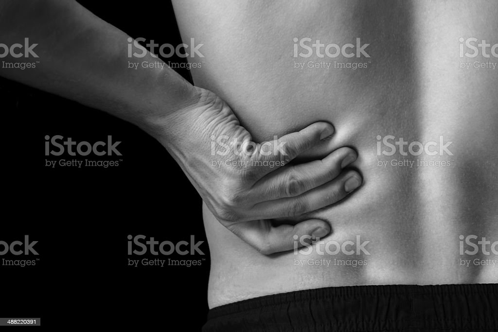 Pain in the lower back, close-up stock photo