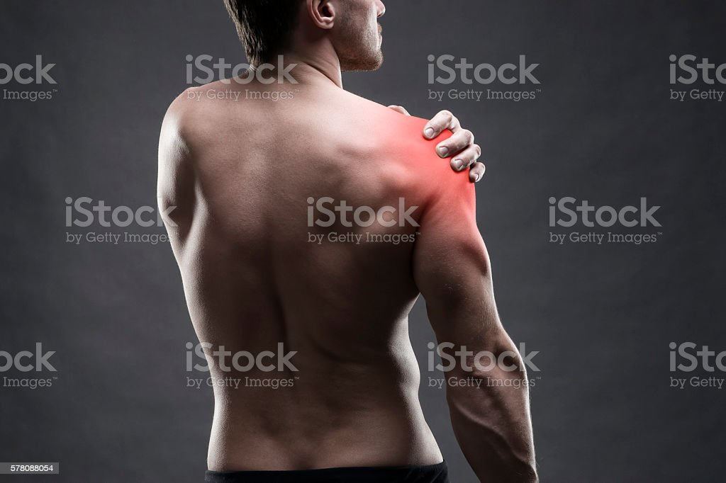 Pain in the shoulder. Muscular male body. stock photo