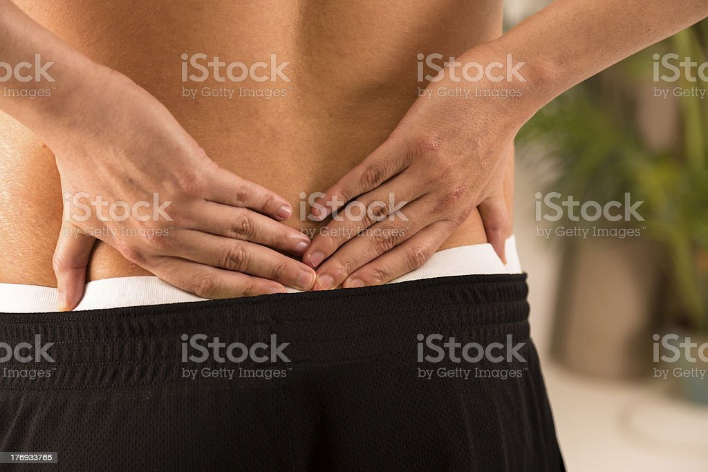 Pain:  Man in sportswear holding lower back that aches. royalty-free stock photo