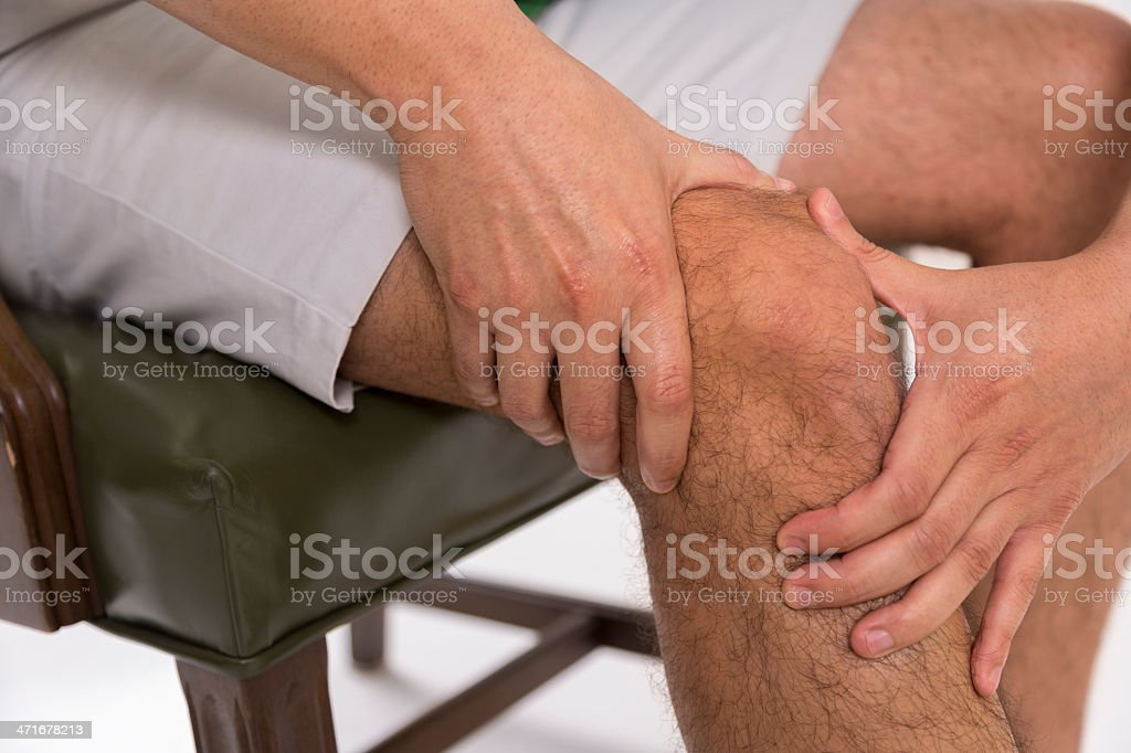 Pain:  Man massaging his painful knee. royalty-free stock photo